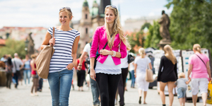 Two female tourists walking along the Charles Bridge while sight