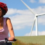 Woman biking / wind turbine