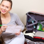 Young woman packing suitcase