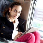 Young woman using tablet computer on the train