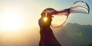 The groom and the bride kiss in mountains against a decline.
